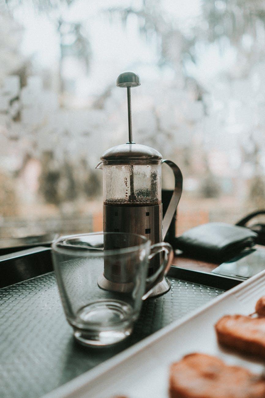 empty cup beside coffee press
