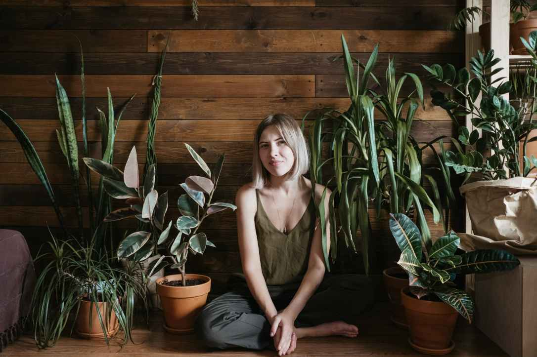woman sits on the floor between indoor plants