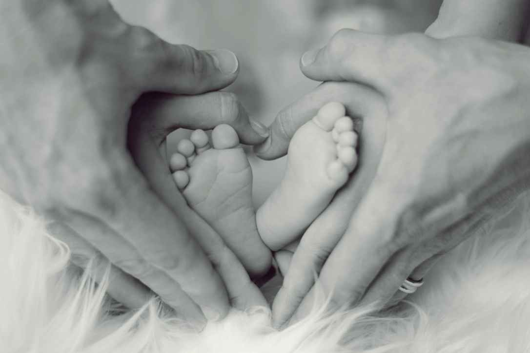 grayscale photo of baby feet with father and mother hands in heart signs