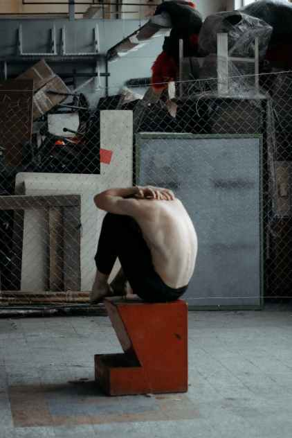 topless man sitting on brown and black block